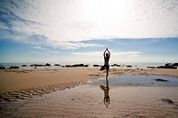 Back view of a woman practicing yoga on a beach