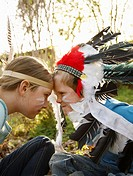 Boy and girl wearing Indian feather headdresses sitting face to face