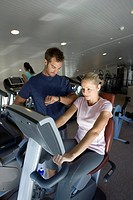 Instructor with woman on exercise machine in gym