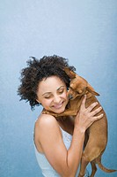 Portrait of woman with curly hair holding dog on light blue background.