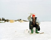 an ice fisherman with a sense of humor, displays his catch on Lake Winnipeg, Manitoba