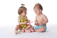 Toddler girl and boy in a bathing suit talking about their sunglasses