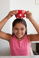 Little teenage girl is carrying a large cup on her head as a joke