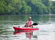 Smiling Black man kayaking on river