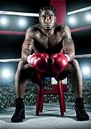 African American boxer sitting in boxing ring
