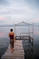 Woman walking on a wooden jetty at sunset, Punta Gorda, Cienfuegos Bay, Cuba.