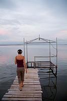 Woman walking on a wooden jetty at sunset, Punta Gorda, Cienfuegos Bay, Cuba.
