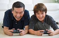 Father and son playing video game on living room floor