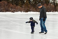 edmonton, alberta, canada, a father skates with his young son in hawrelak park on an outdoor ice rink