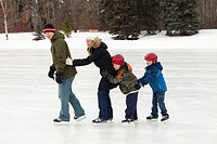 edmonton, alberta, canada, a family skating together on an outdoor ice rink