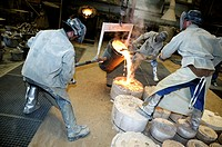 Bronze foundry. Workers pouring molten bronze into moulds. Photographed in Ghent, Belgium.