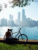 Chicago bicyclist enjoying Chicago summer skyline along Lake Michigan shoreline at Olive Park