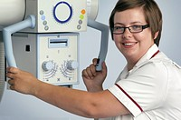Radiographer and X_ray machine. Radiographer holding the device that produces X_rays for use in X_ray imaging procedures.