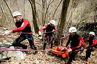 Mountain rescue workers stretchering a casualty to safety through some woods. Photographed in Italy.