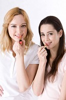 Two women applying lipstick