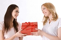 Two young women holding a box of present