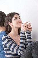 Young woman sitting back to back with boyfriend, drinking coffee