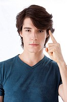 Young man pointing at head, looking at camera (thumbnail)
