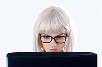 Young woman wearing glasses looking at laptop