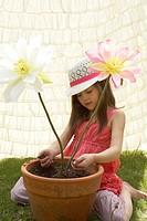 Girl playing with fake flowers in a flower pot