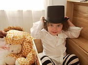Toddler boy in a dressup box playing
