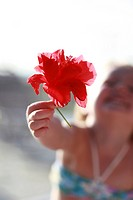 Young girl holding red flower