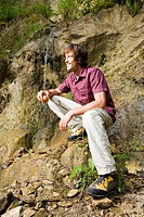 Young man in mountains, sitting by water fall