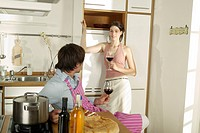 Young couple drinking wine in kitchen