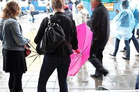 Streetscene during a rainy day, young women unfold their umbrella before crossing the street, Amsterdam, Netherlands