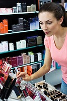 Young woman browsing cosmetics in store