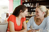 Female friends together at cafe, laughing