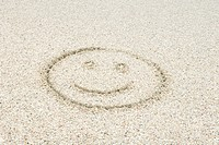 Smiley face drawn in sand at the beach