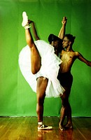 Female ballet dancer holding hand of a male ballet dancer and raising her leg