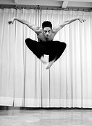 Male dancer jumping in a studio