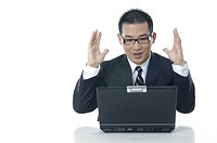 Businessman working on a laptop and raising his hands