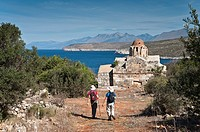 Walkers aproaching the little Byzantine church of Vlacherna near Mezapos in the Deep Mani, Southern Peloponnese, Greece