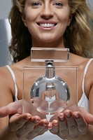 Portrait of smiling woman holding a perfume bottle with her refelction in it