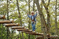 BOY CROSSING A LOG BRIDGE, AERIAL FOREST PARK ACROBRANCHE ON THE ROCHE D´OETRE, SAINT_PHILBERT SUR ORNE, SWISS NORMANDY, ORNE 61, FRANCE