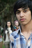 Portrait of young Indian man outdoors, women in background.