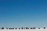 Land vehicles on desert against clear blue sky