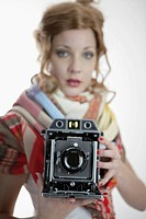 Portrait of beautiful young woman using instant camera
