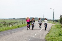 Girls biking side by side on the dike, going home after school, Netherlands