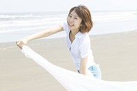Portrait of young woman smiling at beach, holding cloth