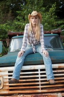 Woman sitting on vintage truck