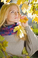 Portrait of young blonde woman standing among colorful autumn leaves