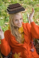 Young blonde woman sitting in wheelbarrow balancing books on her head outdoors