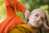 Close_up portrait of young blonde woman with hand behind head outdoors