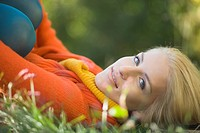 Portrait of smiling young woman lying in grass