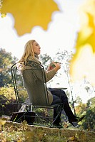 Portrait of young woman drinking cup of tea outdoors on autumn day