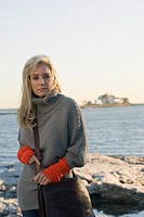 Portrait of stylish young woman in grey sweater standing in coastal landscape